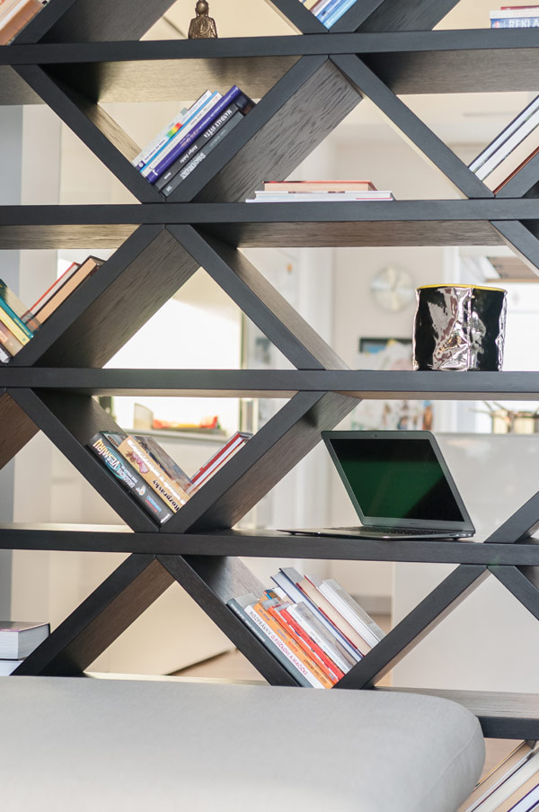 A cool bookshelf that divides the kitchen and living area