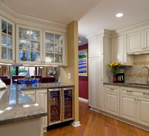 Beautiful frosted glass cabinets and mini beverage cooler fit in aptly in this kitchen