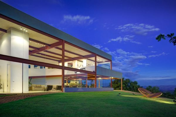 Beautifully lit house in the evening Contemporary Brazilian Home Promises Spectacular View And A Stunning Art Gallery