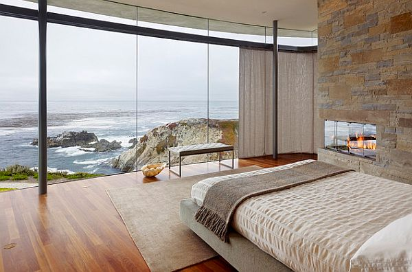 Bedroom with a view of the beach sports a modern fireplace