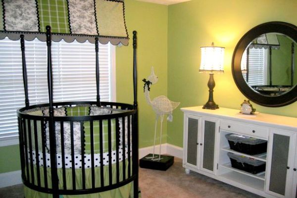 Boys' nursery with a unique green theme and a round crib