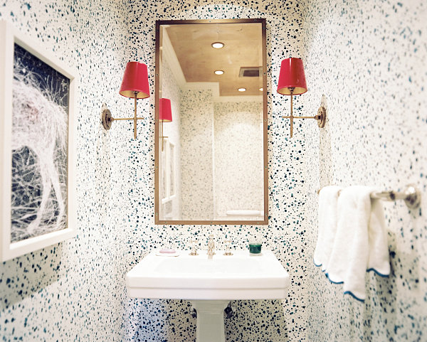 Colorful sconces in a wallpapered bathroom