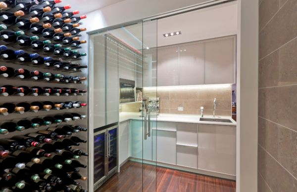 Compact white kitchen separated from wine cellar using sliding glass doors