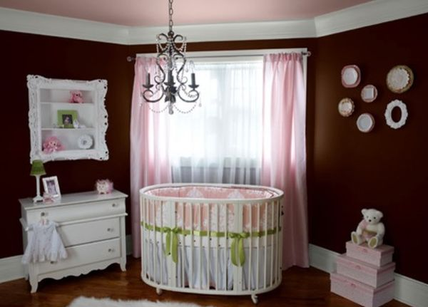 Dark brown walls clubbed with pink accents for a baby girl nursery