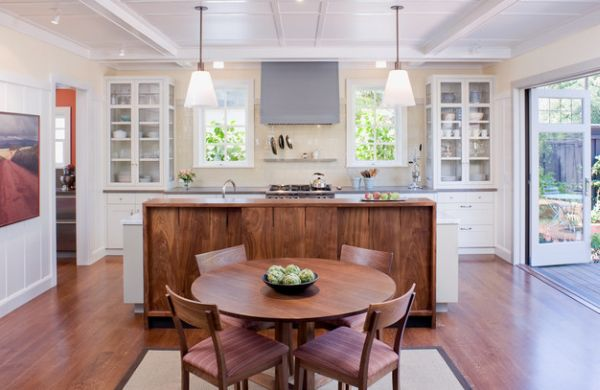 Glass shelves on either side bring symmetry to this kitchen in white
