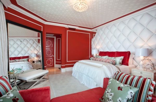 Hollywood Regency style bedroom with rich textiles and tufted wall along with bright red hues