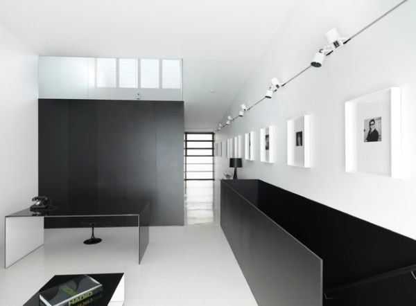 Minimalist interiors with a long gallery wall illuminated by track lighting