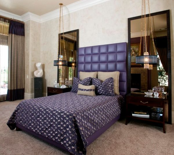 Tufted purple headboard and interesting lighting give this master bedroom Hollywood Regency style