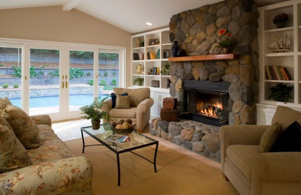 Well ventilated living room with a stone fireplace that sports daft glass doors