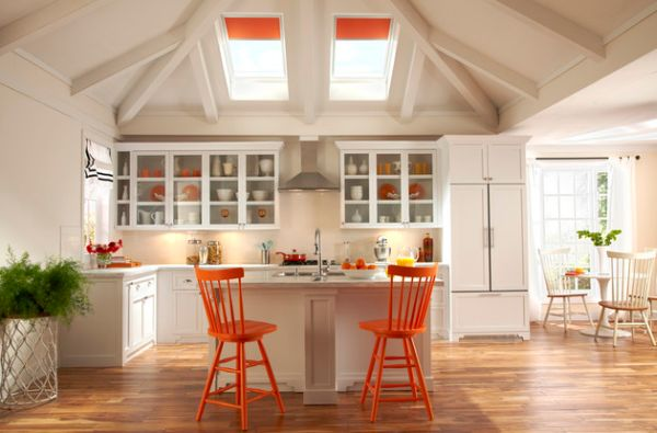 Airy white kitchen employs skylights with orange blinds along with chairs in similar hue