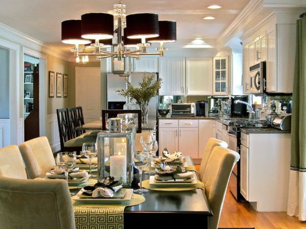 Chandelier with black lampshades above green dining space