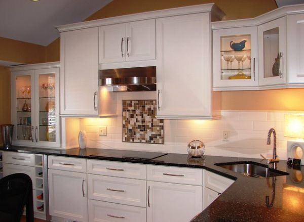 Compact corner sink in a kitchen with dark countertop and white cabinets