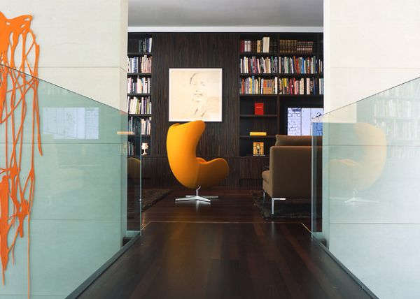Home library in dark tones sports a charming Egg chair by Arne Jacobsen in bold orange