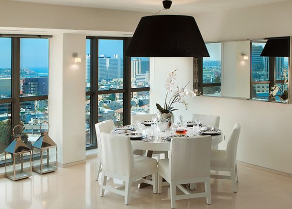 Large pendant light with black lampshade above a pristine white dining space