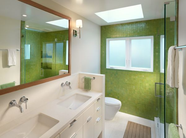 Lime green tile wall and the mirror accentuate the appeal of this bathroom