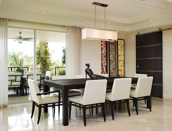 Modern dining area and patio connected with sliding glass doors hidden behind white curtains