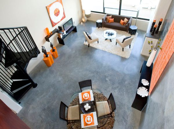 Pop of orange spread throughout the living room with a high ceiling