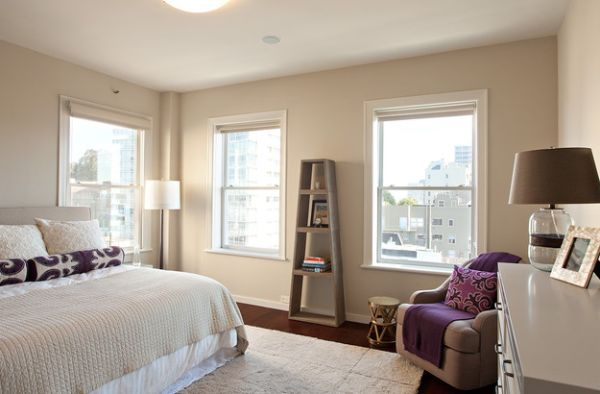 Simple use of purple pillow and rug to offer visual contrast in a neutral setting