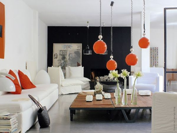 Unique pendant lighting in orange steals the show in this living space