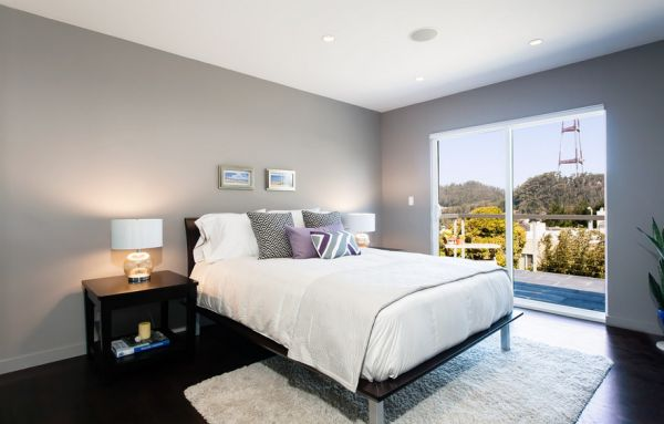 Ample natural ventilation gives the bedroom in light gray an airy appeal