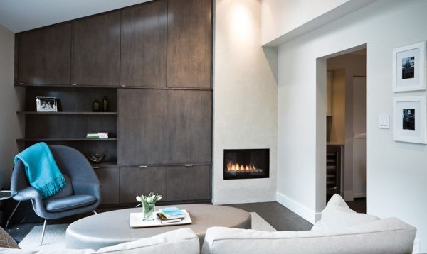 Angled cabinets and the compact fireplace make an interesting background for the womb chair