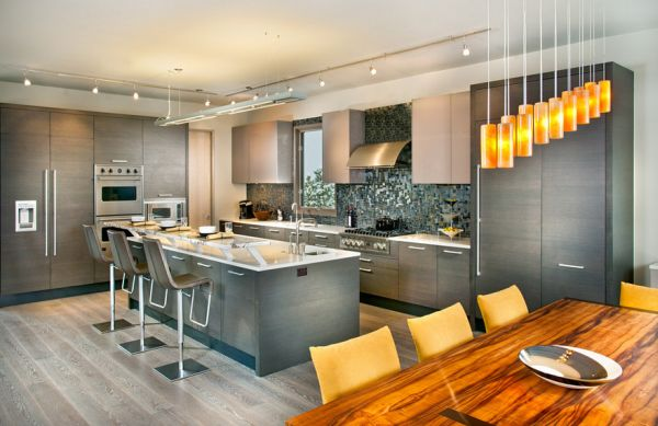 Beautiful lighting and dining area complement the kitchen in gray aptly