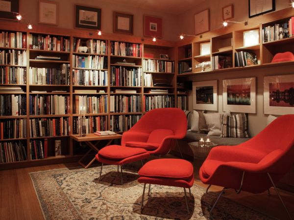 Couple of red womb chairs in the family space seem almost overwhelming