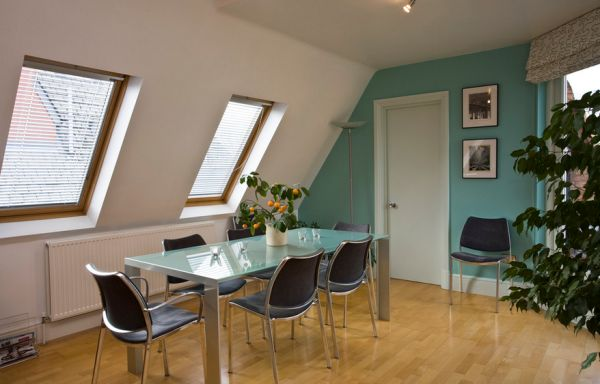 Glass-topped table and an accent wall in the dining area bring in aqua-tinted turquoise