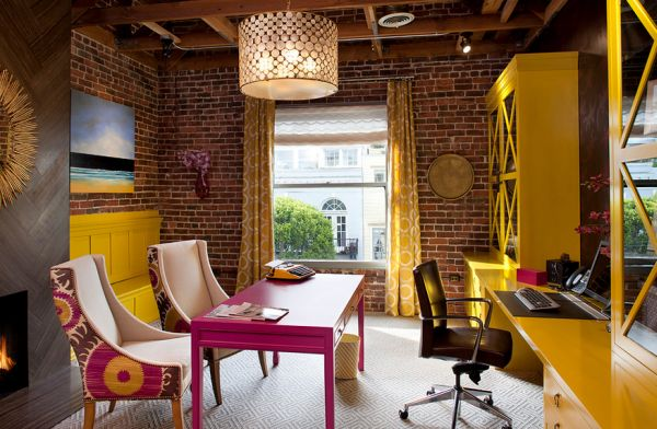 Home office sports exposed brick walls along with shades of fuchsia and yellow