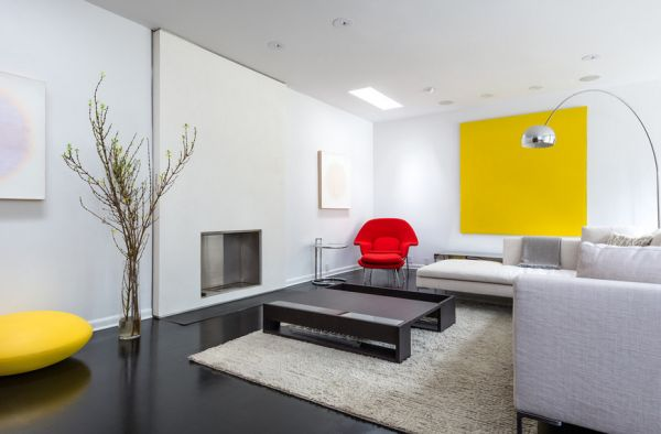 Minimalist living room in white and gray with the womb chair adding a splash of red
