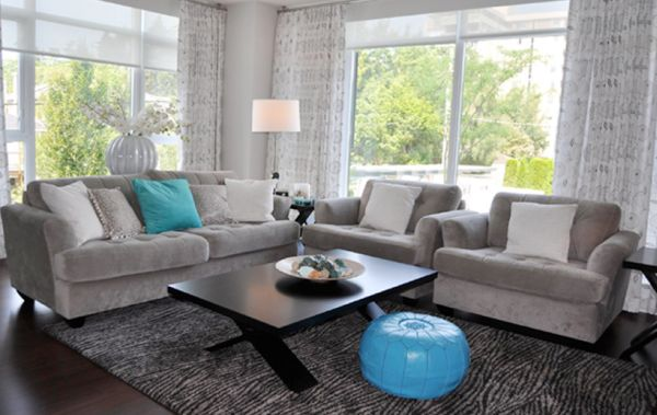 Moroccan pouf and turquoise accents shine in a gray living room