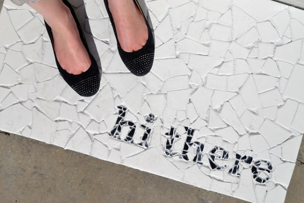 Mosaic tile welcome mat with black words