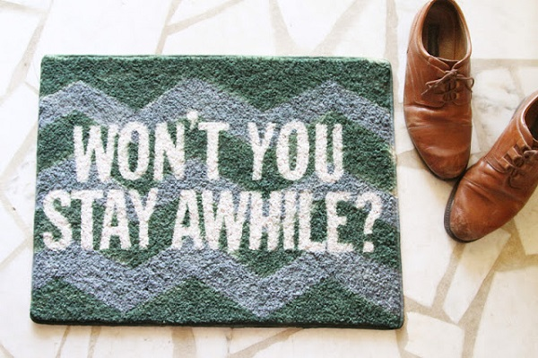 Painted welcome mat with white words