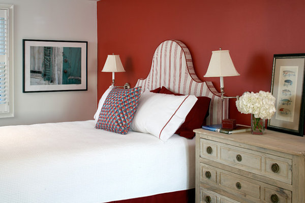 Red accent wall in a crisp bedroom