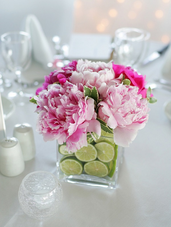 Vase centerpiece filled with fresh flowers and lime slices