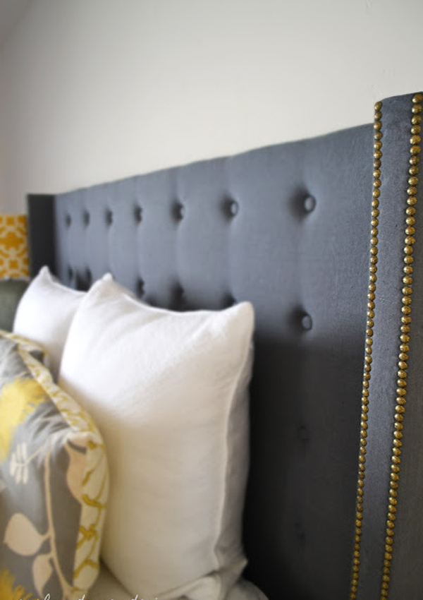 Blue upholstered headboard with gold nailheads