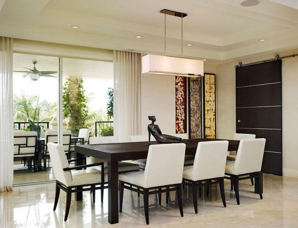 Clean dining area with low profile recessed lighting and large pendant light