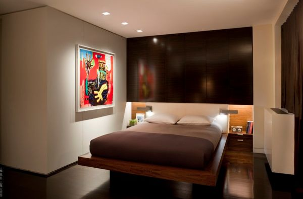Minimalist bedroom with recessed lights highlighting colorful piece of modern art