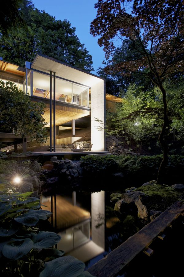 Modern house surrounded by lush green vegetation and maple trees
