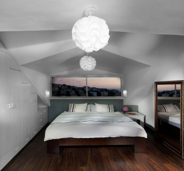 Pendant lights, mirror and the window above the bed bring in a sense of openness