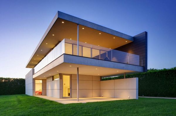Verandas and eaves with recessed lighting give the facade a soft and inviting aura