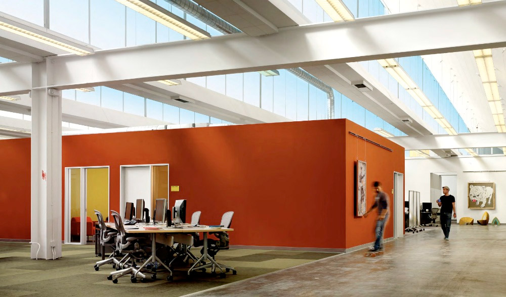 Bright orange conference room structure sits in the middle of an open area via bustler