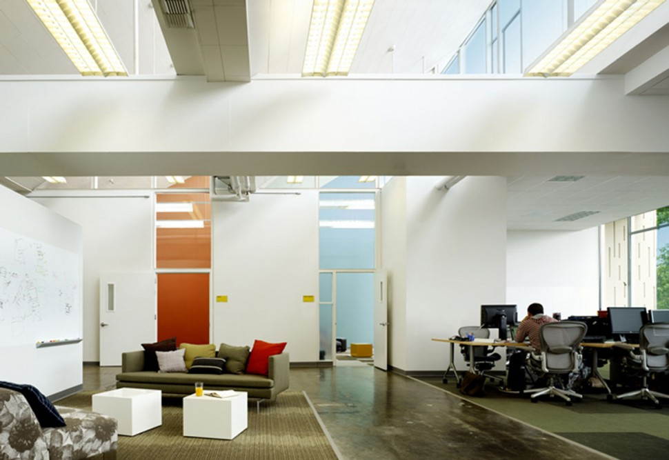 Two enclosed offices add splashes of color to open office and sitting area