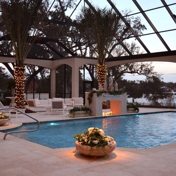 Serene pool with a lovely fireplace next to it