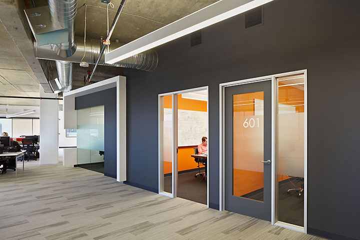 Two bright orange offices add color to the gray wall