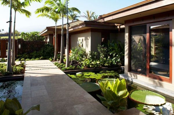 Tropical landscape with a koi pond and a broad walkway