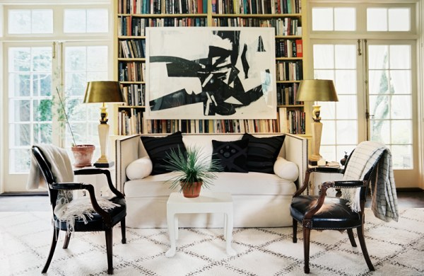 Artwork hangs over a living room bookshelf
