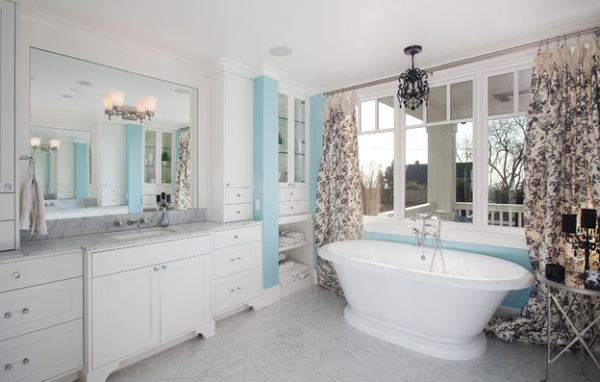 Bathroom in blue and white with toile fabric drapes that anchor the color scheme