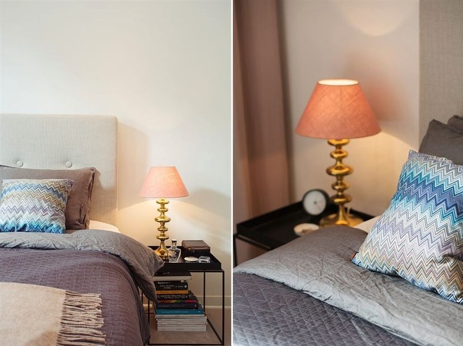 Brass table lamp brings metal accents to the bedroom