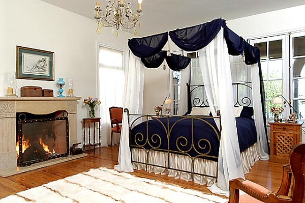 Delazious wrought iron canopy bed with blue and white bedding and fireplace